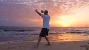 Sportive man som öva Tai Chi på kusten på soluppgång arkivfilmer