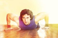 Sportive man som gör liggande armhävningar royaltyfri bild