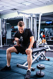 Sportive man in sportswear lifting some weights. And working on his biceps in a gym Royalty Free Stock Images