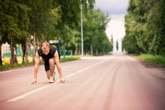Sportive man in starting position prepared to run Stock Image