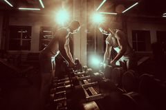 A sportive man in a T-shirt standing in front of a mirror takes dumbbells in the gym. Toned image. stock photo