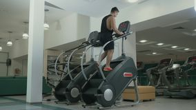 Sportive man training legs on staircase in the gym. Muscular sportive man has a sport exercises in the gym. Handsome guy is moving up stairs and looks forward stock video footage