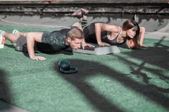 Sportive man and woman doing push ups. Royalty Free Stock Photos