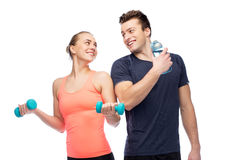 Sportive man and woman with dumbbell and water Royalty Free Stock Photo