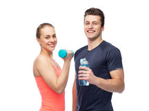 Sportive man and woman with dumbbell and water. Sport, fitness, lifestyle and people concept - happy sportive men and women with dumbbell and water bottle Royalty Free Stock Photography