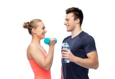 Sportive man and woman with dumbbell and water. Sport, fitness, lifestyle and people concept - happy sportive men and women with dumbbell and water bottle Stock Image