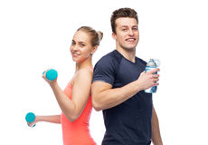 Sportive man and woman with dumbbell and water Royalty Free Stock Photography