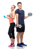 Sportive man and woman with dumbbells. Sport, fitness, lifestyle and people concept - happy sportive men and women with dumbbells flexing muscles Stock Images