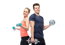 Sportive man and woman with dumbbells. Sport, fitness, lifestyle and people concept - happy sportive men and women with dumbbells flexing muscles Royalty Free Stock Photography