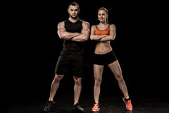 Sportive man and woman posing together and looking at camera. Sportive men and women posing together and looking at camera isolated on black Stock Images