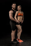 Sportive man and woman posing together and looking at camera. Sportive men and women posing together and looking at camera isolated on black Stock Photography