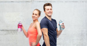 Sportive man and woman with water bottles Stock Images
