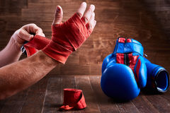 Sportive man wrapping his hands with bandage and boxing gloves on wooden plank. Sportive man wrapping her hands with bandage tape and boxing gloves on wooden Royalty Free Stock Photo