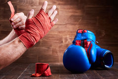 Sportive man wrapping his hands with bandage and boxing gloves on wooden plank. Royalty Free Stock Image