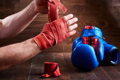 Sportive man wrapping his hands with bandage and boxing gloves on wooden plank. Royalty Free Stock Images