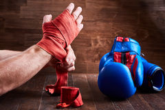 Sportive man wrapping his hands with bandage and boxing gloves on wooden plank. Stock Photos