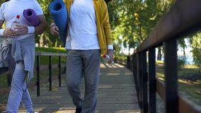 Sportive mature men walking in park with yoga mats and water bottles, workout. Stock photo royalty free stock images
