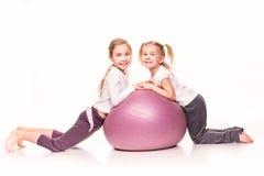 Sportive Mädchen auf einem Sitzball lokalisiert über Weiß Stockfotos