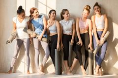 Sportive multiracial girls talk laughing waiting for yoga class