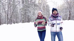 Sportive nice couple jogging in the snowbound forest and enjoying their time. Sportive nice couple jogging together in the snowbound forest on a beautiful winter stock video