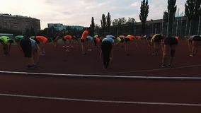 Sportive people group doing squats and stretching backs at stadium stock video