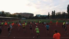 Sportive people group stretching ankles at stadium in dormitory area stock footage