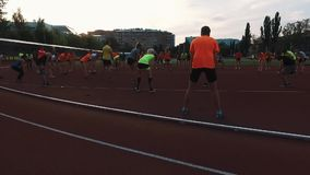 Sportive people group stretching knees at stadium in dormitory area stock footage