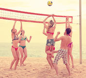 Sportive people playing volley on beach. Sportive active adults playing volleyball on a beach near ocean Stock Images