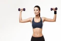 Sportive piękna dziewczyna w sportswear szkolenia rękach z dumbbells nad białym tłem obrazy stock