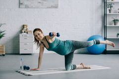 Sportive pregnant woman exercising with dumbbells. In living room royalty free stock photos