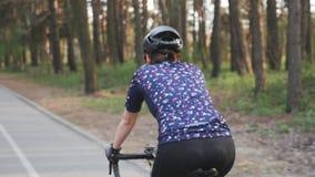 Sportive Radfahrerfrau, die Fahrrad im Park fährt Rückseite folgen Schuss Radfahrenkonzept