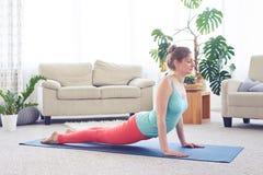 Sportive relaxed woman doing upward-facing dog pose Stock Photo