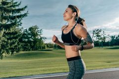 Sportive running woman in earphones. Side view of sportive woman in earphones running in park Stock Image