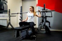 Sportive sérieuse s'asseyant dans un gymnase sur un simulateur image stock