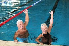 Sportive senior couple doing exercises. In indoor swimming pool stock photography