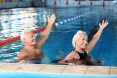 Sportive senior couple doing exercises in indoor. Swimming pool stock photo