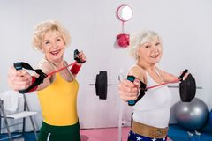 Sportive senior ladies exercising with resistance bands and smiling. At camera stock image