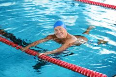 Sportive senior man in indoor pool royalty free stock photography