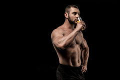 Sportive shirtless man drinking juice isolated on black. Side view of sportive shirtless man drinking juice isolated on black Stock Photo