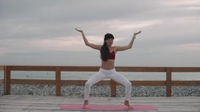 Brunette woman is performing traditional pose of hatha yoga outdoors in daytime stock video footage
