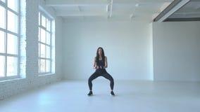 Sportive sprawności fizycznej kobieta w sportswear robi kucnięciom w białym studiu footage zbiory wideo