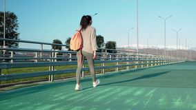 Sportive teen girl is walking in open sport stadium, camera is following her. Cheerful young schoolgirl is going on training in stadium on open air. She is stock video