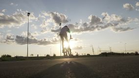 Sportive teenager relaxing on bike riding and doing tricks with sunset in background -. Sportive teenager relaxing on bike riding and doing tricks with sunset in stock footage