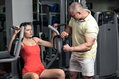 Sportive trainer forses woman to do exercise Royalty Free Stock Photo