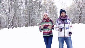 Sportive trevliga par som joggar i den insnöade skogen och tycker om deras tid stock video
