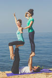 Sportive trio group are doing acroyoga on the Royalty Free Stock Photos