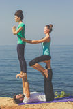 Sportive trio group are doing acroyoga on the Royalty Free Stock Images