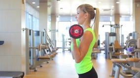 Sportive ung kvinna som gör övning med skivstången lager videofilmer