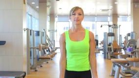 Sportive ung kvinna som gör övning med skivstången arkivfilmer