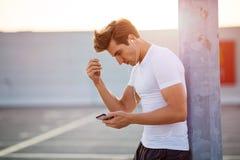 Sportive ung man i staden med smartphonen royaltyfri fotografi